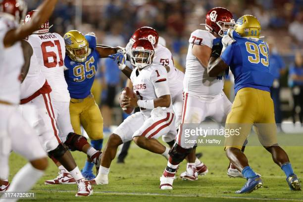 Jalen Hurts of the Oklahoma Sooners escapes pressure from Jason Harris and Elijah Wade of the UCLA Bruins during the second half of a game at the...