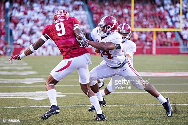 Jalen Hurts runs for a touchdown behind the blocking of Damien Harris of the Alabama Crimson Tide on Santos Ramirez of the Arkansas Razorbacks at...