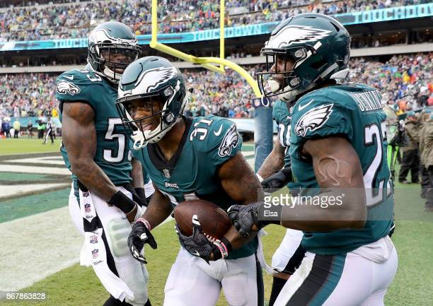 Jalen Mills of the Philadelphia Eagles is congratulated by teammates Nigel Bradham and Malcolm Jenkins after Mills picked off a pass from CJ Beathard...