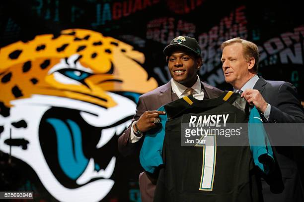 Jalen Ramsey of the Florida State Seminoles holds up a jersey with NFL Commissioner Roger Goodell after being picked overall by the Jacksonville...
