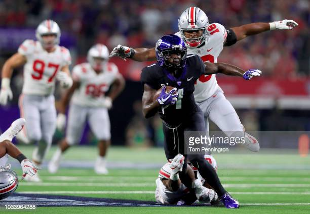 Jalen Reagor of the TCU Horned Frogs carries the ball against Damon Arnette Jr of the Ohio State Buckeyes and Jonathon Cooper of the Ohio State...