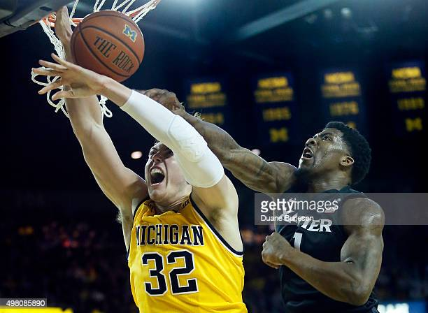Jalen Reynolds of the Xavier Musketeers blocks a shot from behind on Ricky Doyle of the Michigan Wolverines during the first half at Crisler Arena on...