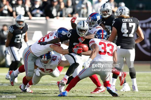 Jalen Richard of the Oakland Raiders is tackled by Rhett Ellison, Ray-Ray Armstrong and Andrew Adams of the New York Giants at Oakland-Alameda County...