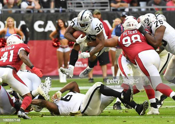Jalen Richard of the Oakland Raiders leaps over teammate Ian Silberman while running the ball against the Arizona Cardinals during the first half at...