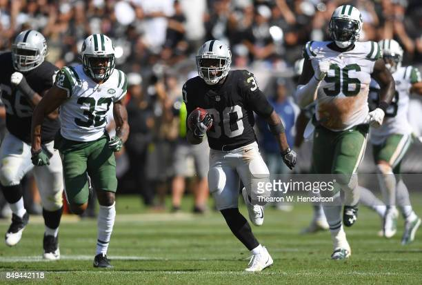 Jalen Richard of the Oakland Raiders scores on a 52 yard touchdown run while pursued by Juston Burris of the New York Jets during the fourth quarter...