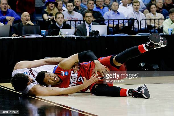 Jalen Robinson of the Dayton Flyers and Stefan Nastic of the Stanford Cardinal battle for a loose ball during a regional semifinal of the 2014 NCAA...