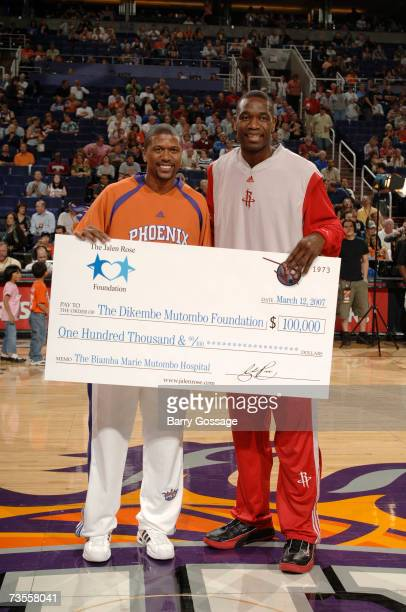 Jalen Rose of the Phoenix Suns presents Dikembe Mutombo of the San Antonio Spurs with a check for $100000 for the Dikembe Mutombo Foundation before...