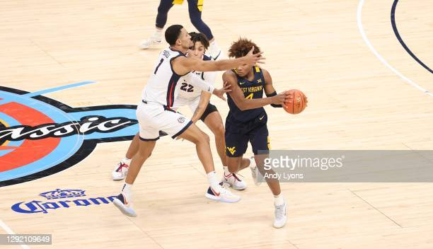 Jalen Suggs and Anton Watson of the Gonzaga Bulldogs defend Miles McBride of the West Virginia Mountaineers during the Jimmy V Classic at Bankers...