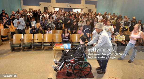 BEACH CALIF USA Jalen Thayer being pushed by his grandfather Matthew Thayer gets a standing ovation as he enters the auditorium at Patrick Henry...