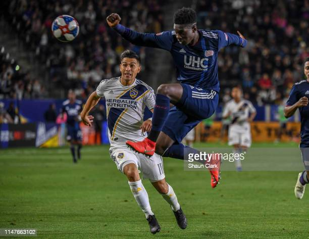 Jalil Anibaba of New England Revolution clears the ball from Favio Alvarez of Los Angeles Galaxy during the Los Angeles Galaxy's MLS match against...