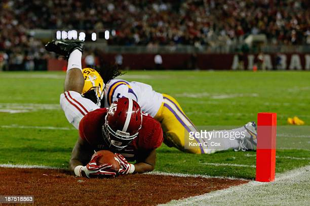 Jalston Fowler of the Alabama Crimson Tide dives for a touchdown against Craig Loston of the LSU Tigers that was called back due to an offensive...