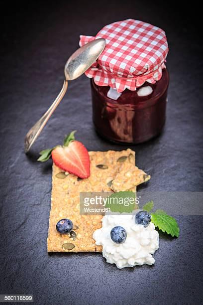 Jam jar, slice of crispbread, curd and fruits on slate