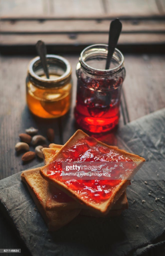 Jam spread on bread with jars filled of jam : Stock Photo