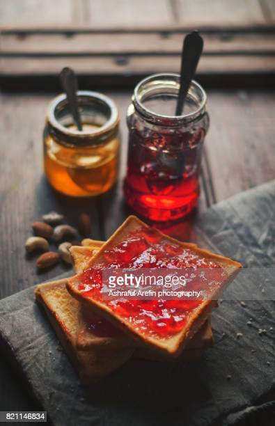 jam spread on bread with jars filled of jam - gelatin dessert stock photos and pictures
