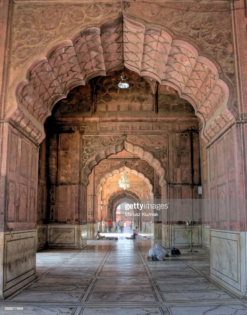 Jama Masjid mosque arches and praying men : Stock Photo