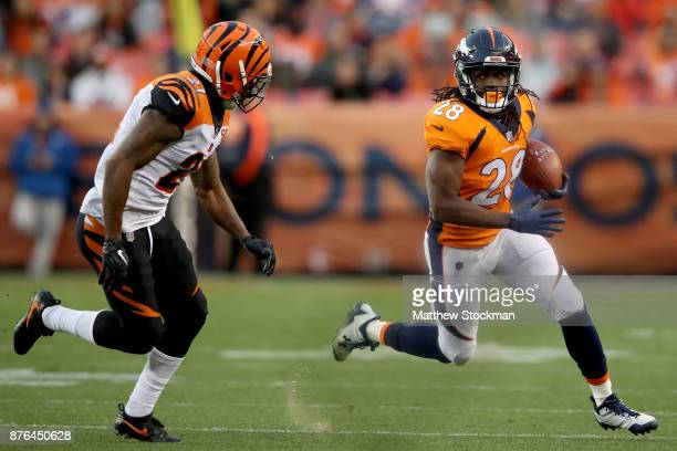 Jamaal Charles of the Denver Broncos attepmts to elude Darqueze Dennard of the Cincinnati Bengals at Sports Authority Field at Mile High on November...