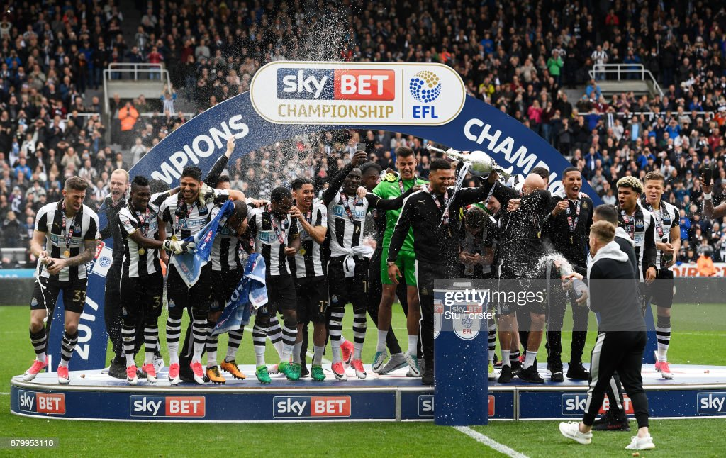 Jamaal Lascelles of Newcastle United (L) and Jonjo Shelvey of Newcastle United (R) celebrate with the Championship Trophy after the Sky Bet Championship match between Newcastle United and Barnsley at St James' Park on May 7, 2017 in Newcastle upon Tyne, England. Newcastle United are crowned champions after a 3-0 victory.