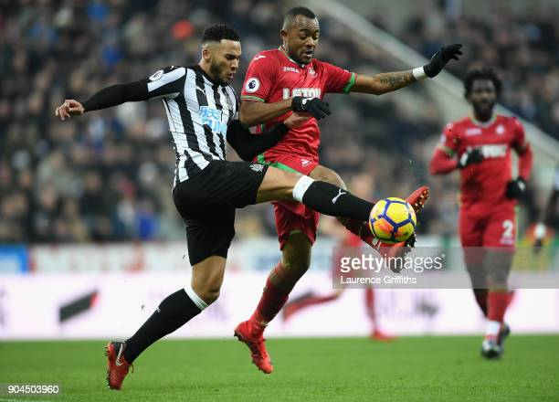 Jamaal Lascelles of Newcastle United challenges Jordan Ayew of Swansea City during the Premier League match between Newcastle United and Swansea City...