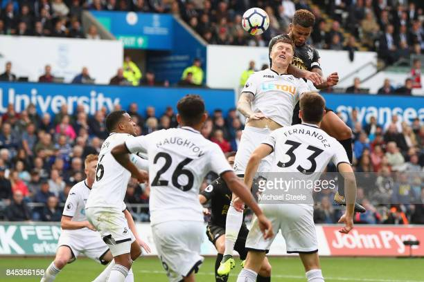 Jamaal Lascelles of Newcastle United rises above Alfie Mawson of Swanseaa City to score his sides first goal during the Premier League match between...