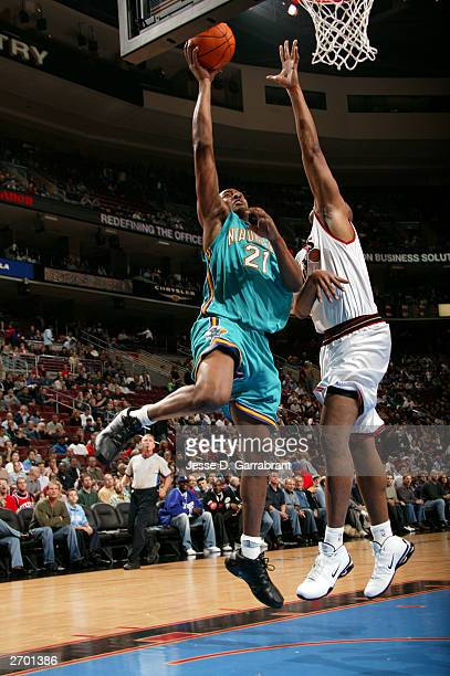 Jamaal Magloire of the New Orleans Hornets attempts a shot Derrick Coleman of the Philadelphia 76ers November 5 2003 at the Wachovia Center in...
