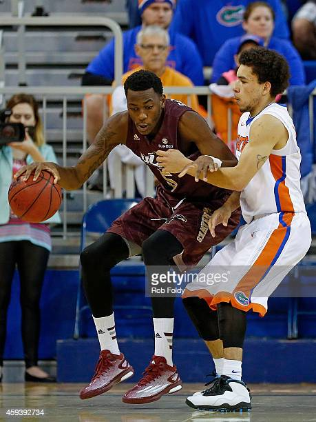 Jamaal Samuel of the Louisiana Monroe Warhawks is defended by Chris Chiozza of the Florida Gators during the second half of the game at Stephen C...