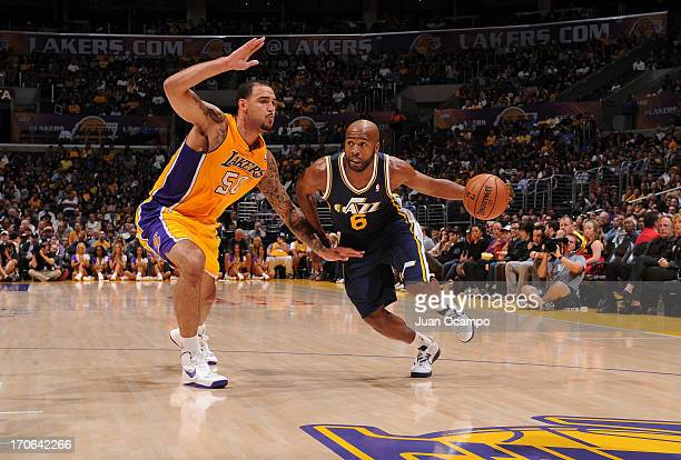 Jamaal Tinsley of the Utah Jazz protects the ball from Robert Sacre of the Los Angeles Lakers during the game between the Utah Jazz and the Los...