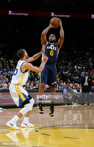 Jamaal Tinsley of the Utah Jazz shoots against Stephen Curry of the Golden State Warriors on April 7 2013 at Oracle Arena in Oakland California NOTE...