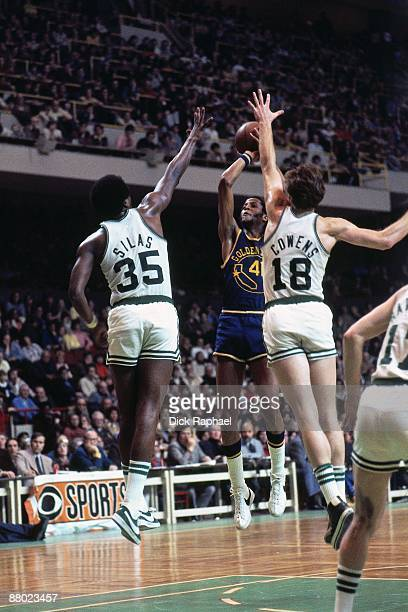 Jamaal Wilkes of the Golden State Warriors shoots a jump shot against Paul Silas and Dave Cowens of the Boston Celtics during a game played in 1975...