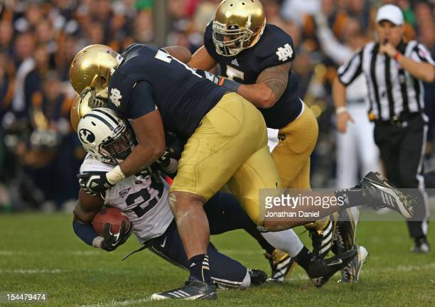 Jamaal Williams of the BYU Cougars is dropped by Stephon Tuitt Louis Nix III and Manti T'eo of the Notre Dame Fighting Irish at Notre Dame Stadium on...