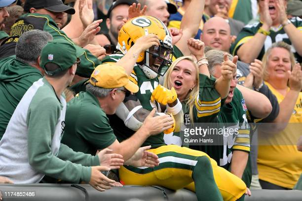 Jamaal Williams of the Green Bay Packers celebrates with fans after scoring a touchdown in the first quarter against the Minnesota Vikings at Lambeau...