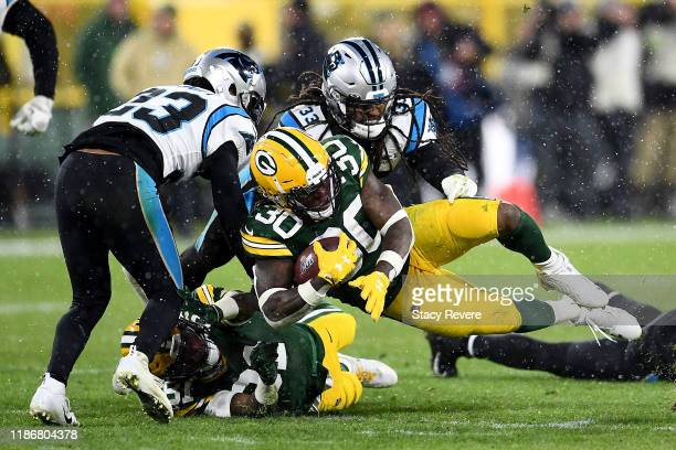 Jamaal Williams of the Green Bay Packers gets tackled by Tre Boston and Javien Elliott of the Carolina Panthers during the third quarter in the game...
