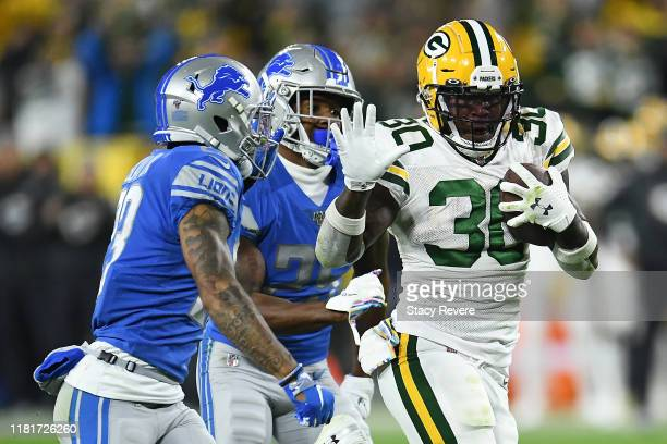 Jamaal Williams of the Green Bay Packers is pursued by Darius Slay of the Detroit Lions during a game at Lambeau Field on October 14 2019 in Green...
