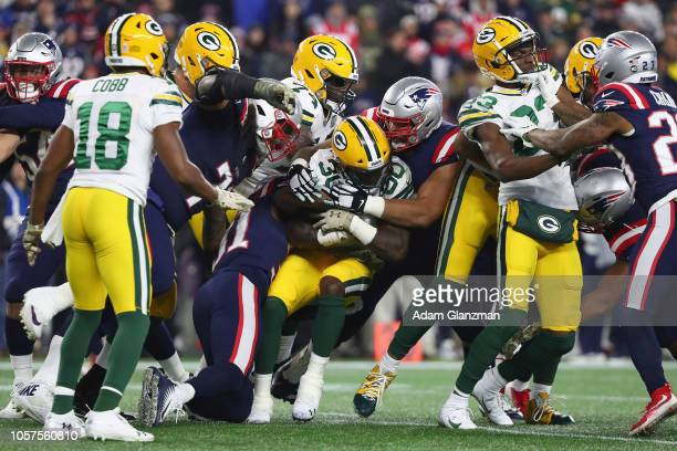 Jamaal Williams of the Green Bay Packers is tackled by the New England Patriots defense during the second half at Gillette Stadium on November 4 2018...