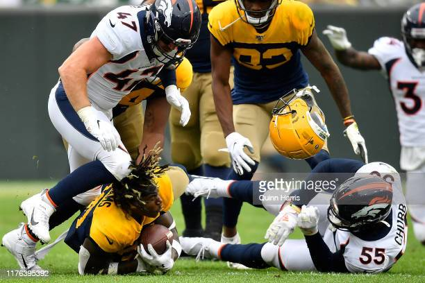 Jamaal Williams of the Green Bay Packers loses his helmet in the second quarter after being tackled by Josey Jewell of the Denver Broncos and Bradley...