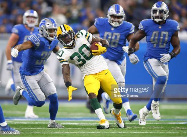 Jamaal Williams of the Green Bay Packers runs for yardage against Jamal Agnew of the Detroit Lions Jeremiah Ledbetter and Jarrad Davis of the Detroit...
