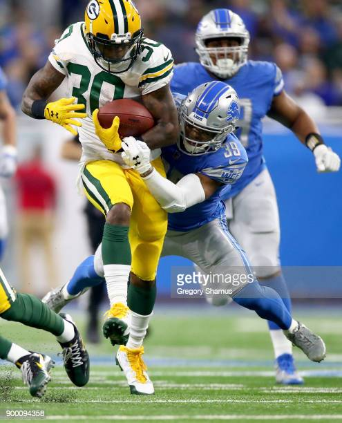 Jamaal Williams of the Green Bay Packers runs for yardage against Jamal Agnew of the Detroit Lions during the first quarter at Ford Field on December...