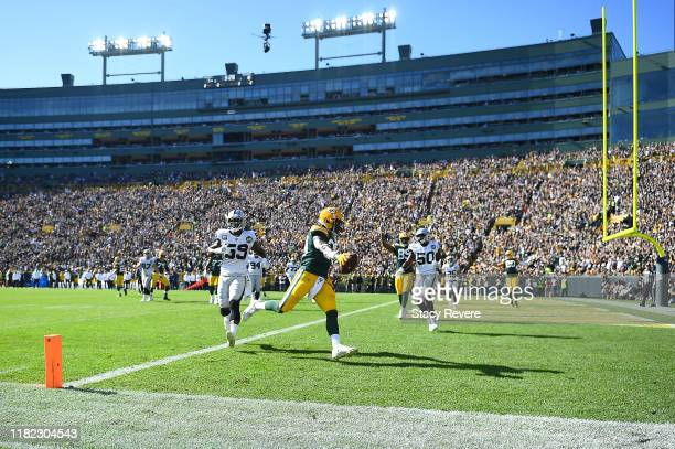 Jamaal Williams of the Green Bay Packers scores a touchdown during the second quarter against the Oakland Raiders in the game at Lambeau Field on...