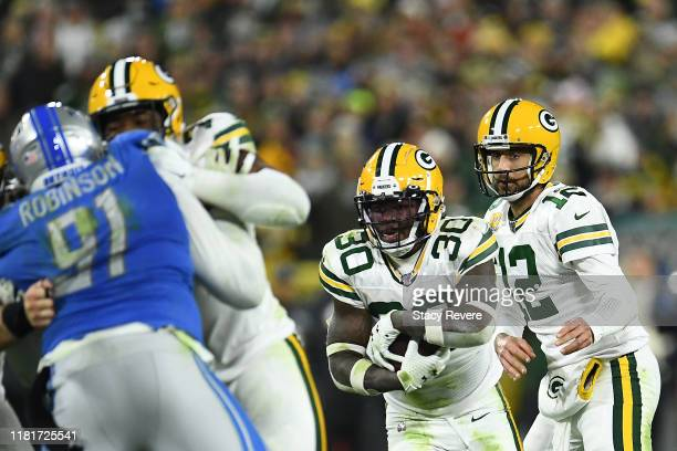 Jamaal Williams of the Green Bay Packers takes the handoff from Aaron Rodgers during a game against the Detroit Lions at Lambeau Field on October 14...