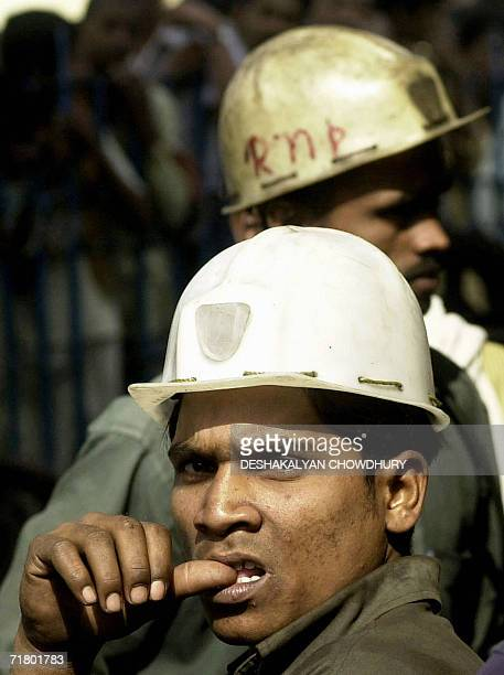 In this photograph dated 21 February 2004, a group of Indian miners wait anxiously at the pit head for news of their colleagues trapped in a mine...