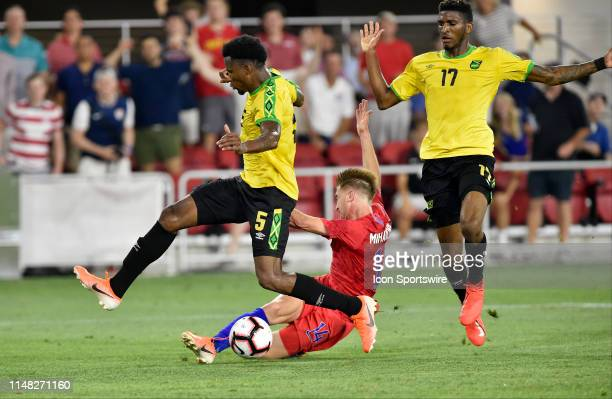 Jamaica defenders Damion Lowe Alvas Powell converge on United States midfielder Djordje Mihailovic as he shoots on goal and during the United States...