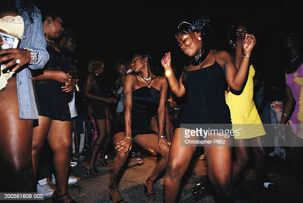 Jamaica, Kingston, group of women dancing in street, night