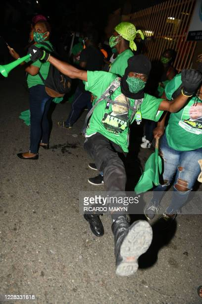 Jamaica Labour Party supporters react while they await the final count of votes for the St. Catherine north west constituency during the general...