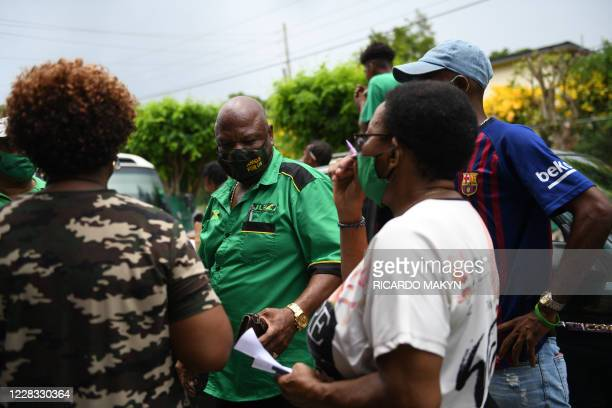 Jamaica Labour Partys Newton Amos stands with supporters at the Mount Rosser Primary and infant school where he cast his ballot in the St. Catherine...