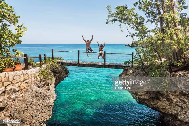 jamaica, negril, people jumping into ocean from footbridge - jamaica stock pictures, royalty-free photos & images