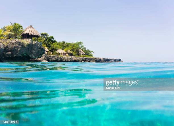 jamaica, negril, traditional huts on rocky coastline - jamaica stock pictures, royalty-free photos & images
