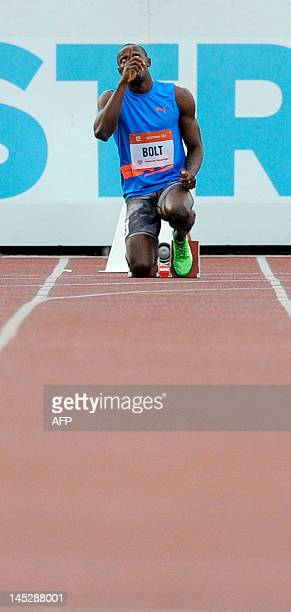 Jamaica sprinter Usain Bolt prays prior to the beginning of the men's 100m race at the Zlata Tretra athletics meeting in the eastern Czech city of...