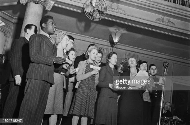 Jamaican actor and baritone singer Uriel Porter , on left, and Welsh actress and singer Doris Hare , 3rd from right, lead the singing of sea songs...