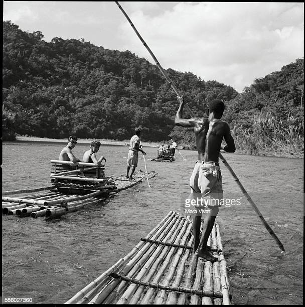 Jamaican boatmen pole through a river as they carry tourists on long narrow bamboo rafts
