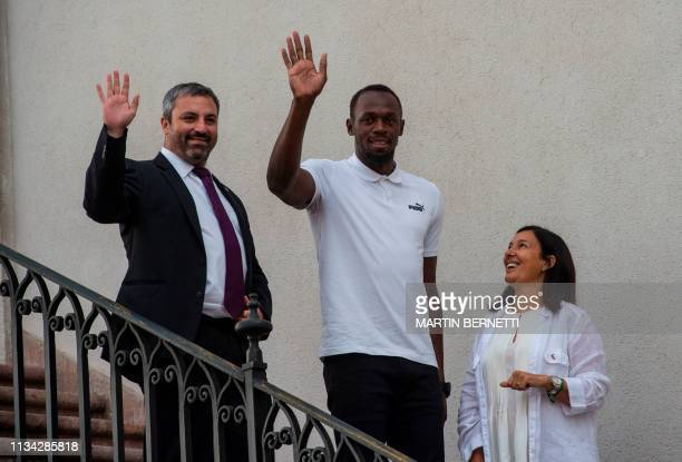 Jamaican eighttime Olympic sprint champion Usain Bolt gestures next to Chilean Sport Minister Paulina Kantor and ViceSport Minister Andres Otero upon...