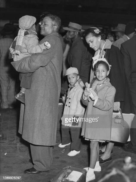 Jamaican family, with the father carrying a small child, on their arrival in England, location unknown, circa 1950.